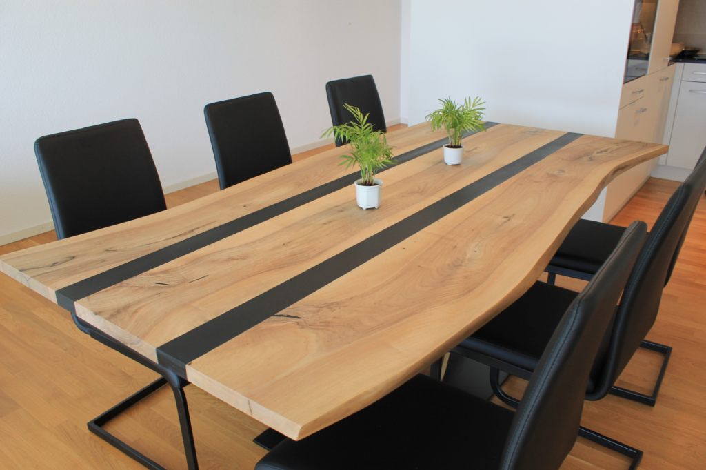 Der massive Nussbaum-Tisch besteht aus einer Nussbaum-Tischplatte und einem Stück Nussbaum-Stamm als Tisch-Bein. Zwei Streifen Epoxidharz verbinden die Holzstücke.
