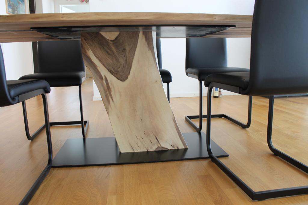 Fuss aus einem Nussbaum Stamm bei einem massiven Nussbaum-Tisch.
