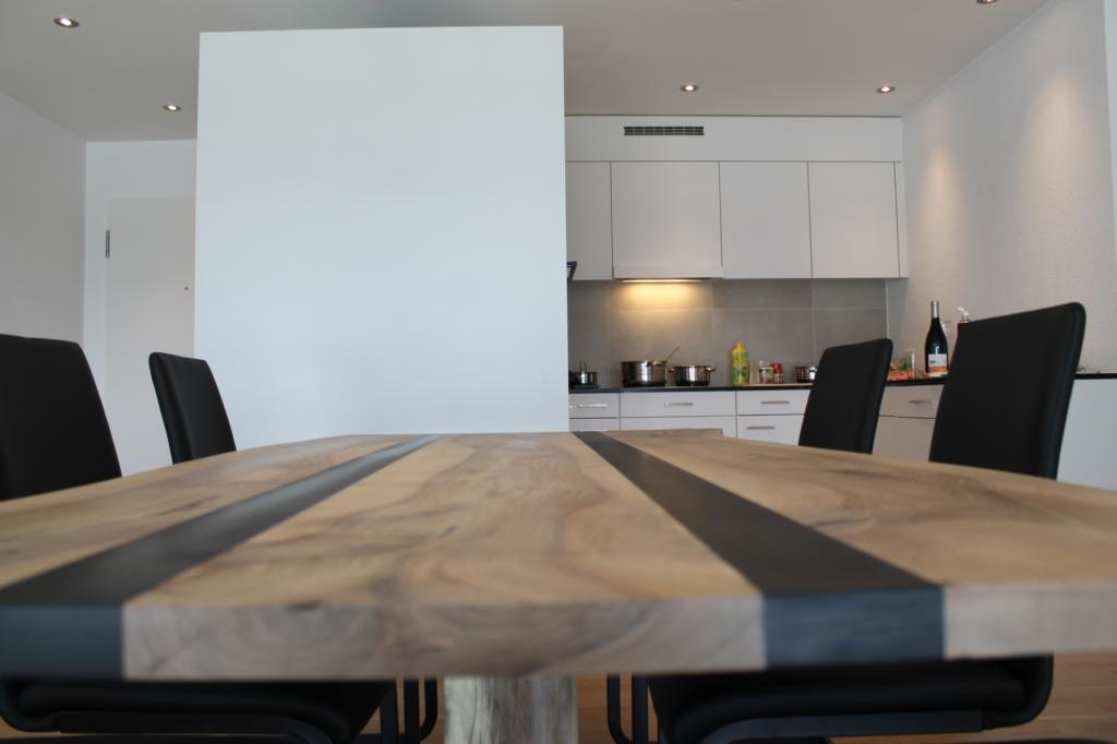 Streifen aus schwarzem Epoxidharz bei einem massiven Nussbaum-Holz-Tisch