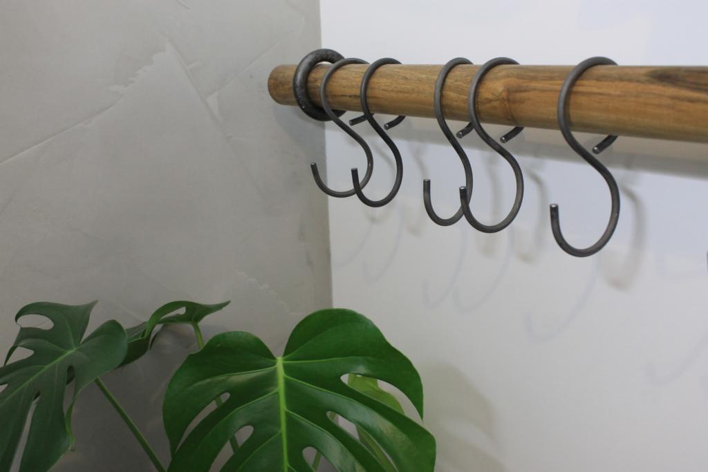 von Hand gebogene S-Haken an einer massiven Holzstange aus Nussbaum