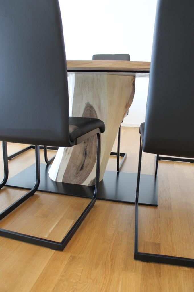 Tischbein eines massiven Nussbau-Holz-Tisch versteckt hinter Stühlen